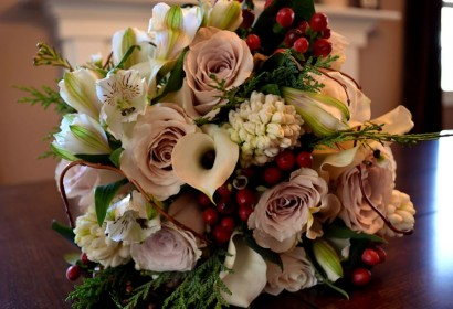 Bridal bouquet with white calla lilies, champagne roses, red hypericum berries, white alstromeria, white hyachinth, and cedar greens.